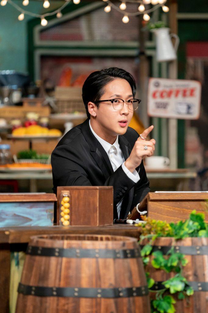 세트 테이블에 앉은 라비가 안경을 쓴 채로 손가락을 가르키며 날카로운 눈빛으로 추리를 펼치고 있다.