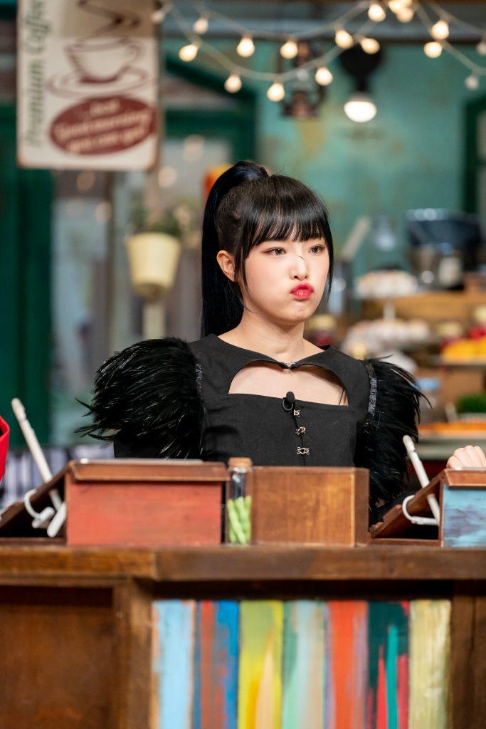 흑조 의상을 입은 최예나가 테이블 의자에 앉아 특유의 뾰루뚱한 표정으로 문제를 보고 있다.