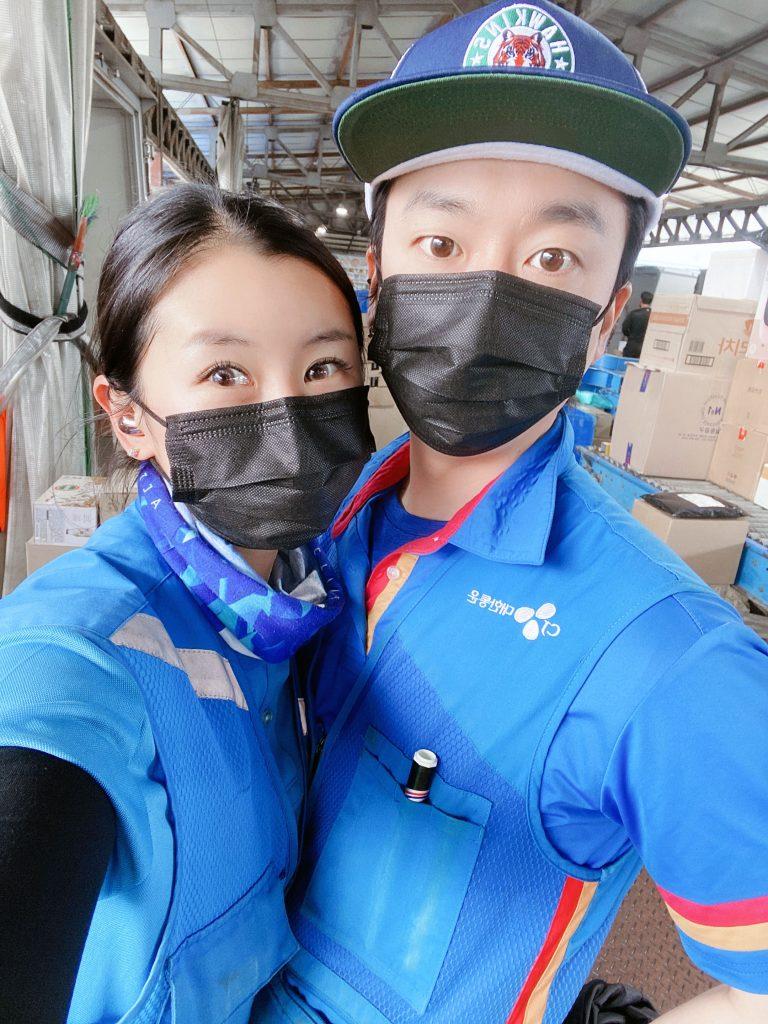CJ대한통운 택배기사 김동훈(37)씨와 아내 배민정(34)씨가 물류 분류 장소를 배경으로 CJ대한통운 파란색 조끼와 검은색 마스크를 쓰고 카메라를 쳐다보고 있다.