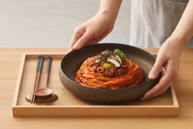 비비고 소고기고추장 비빔 유수면을 요리해 트레이, 수저와 함께 세팅한 이미지.