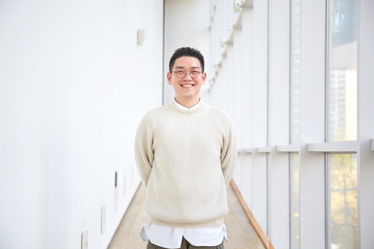티빙 '신서유기 스페셜 스프링 캠프' 박현용 PD가 CJ ENM 상암 본사 창가 복도에서 아이보리 니트를 입고 카메라를 향해 미소를 짓고 있다.