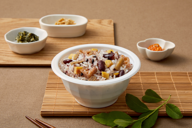 CJ제일제당 햇반솥반 뿌리채소영양밥 이미지로 김밥말이 위에 뿌리채소영양밥이 놓여져 있고, 그 옆에 나무 쟁반 위엔 흰색 그릇에 반찬이 놓여져 있다.