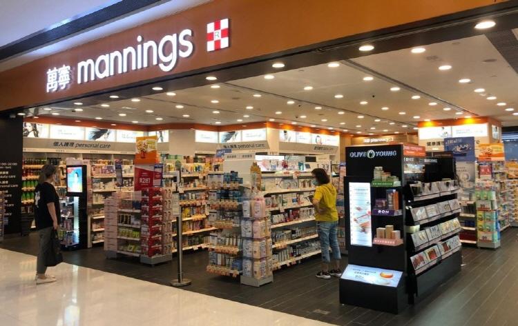 홍콩 매닝스 플래그십 매장 오른쪽에 올리브영 전용 매대가 설치되어 있다. 상단 간판엔 'Mannings'라는 상호명이 붙어 있고, 매장 내 노란색 옷을 입은 여성이 물품을 보고 있고, 매장 외 검은색 옷을 입은 여성이 매장을 들어서려고 하고 있다.