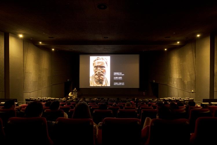 강연 장면으로 스크린에는 다니엘 다 볼테라(Daniele da Volterra)가 만든 '미켈란젤로의 두상' 모습이 보이고 관객들은 이 작품을 바라보고 있다.