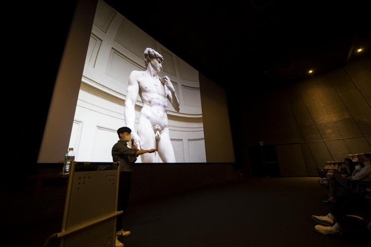 채수한 아트가이드가 스크린에 비춰진 다비드 조각상에 대한 설명을 하고 있다.
