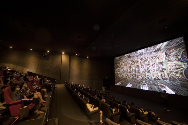 CGV피카디리1958에서 '아트가이드와 함께하는 400년의 서양미술사' 강연 장면으로 스크린에는 미켈란젤로의 천장화가 보여지고 있고, 관객들은 이 작품을 소개하는 채수한 아트가이드의 이야기를 들으며 천장화를 보고 있다.