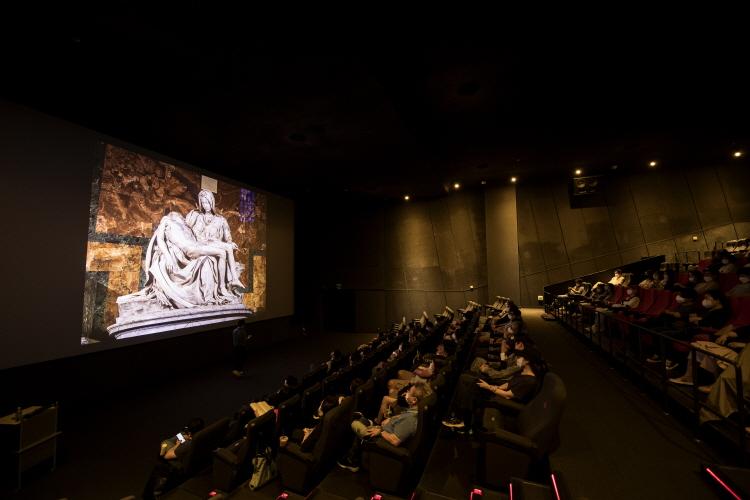 채수한 아트가이드가 스크린에 비춰진 피에타 조각상에 대한 설명을 하고 있고, 관객들은 스크린을 쳐다보며 저마다 감상을 하고 있다.