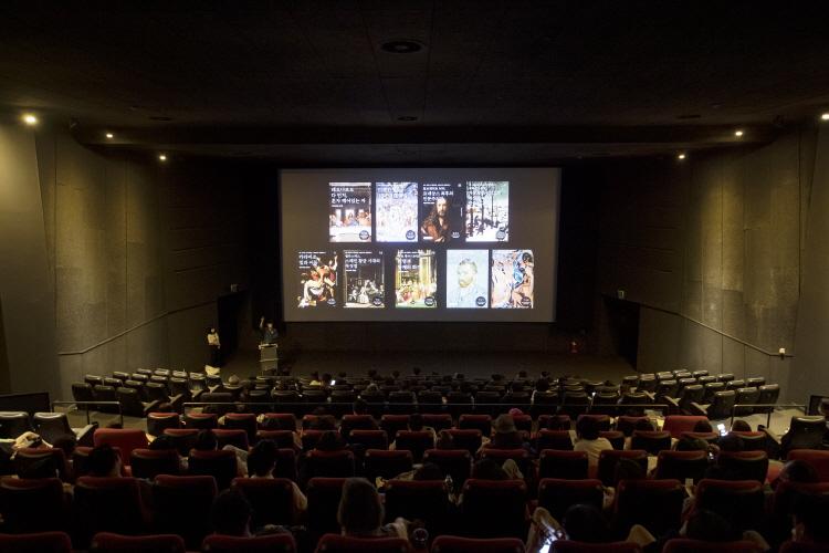 스크린에 레오나르도 다 빈치, 미켈란젤로를 포함한 총 9강의 프로그램 포스터가 비춰졌고, 채수한 아트가이드는 프로그램을 설명을 관객들은 이를 듣고 있다.