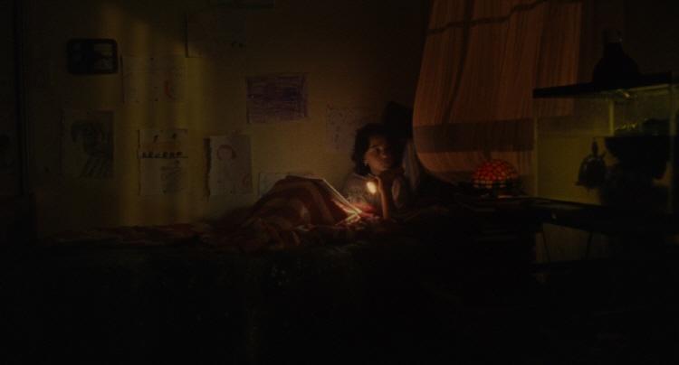 어두운 방에서 손전등 불빛에 의지한 채로 노트를 보고 있는 웬디의 모습이다.