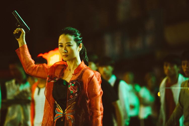 어두운 밤 다운타운에서 붉은색 옷을 입은 영화 '강호아녀'의 주인공 차오가 총을 쏘고 누군가를 응시하고 있다. 뒤에는 다수의 남자들이 이 광경을 목격하고 있다.