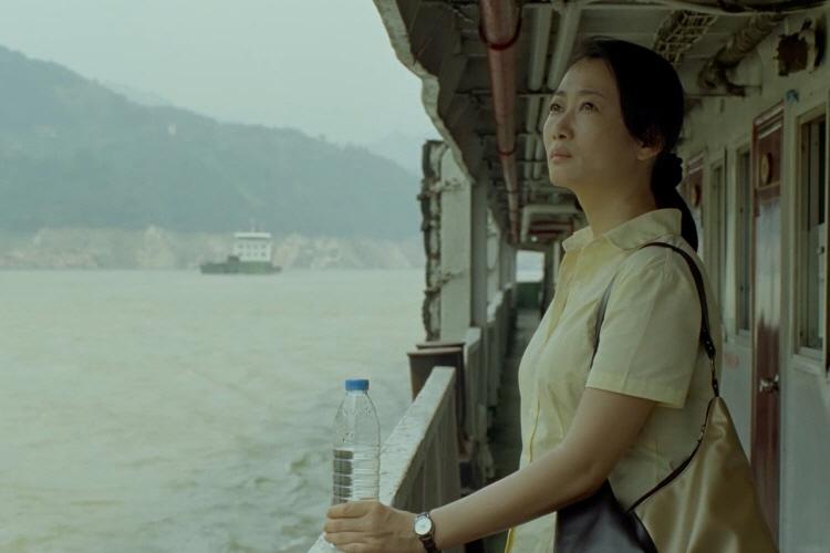 중국 내 강 위 유람선을 탄 차오가 아이보라색 셔츠를 입고, 손목시계를 찬 왼쪽 손으로 물병을 잡은 채 먼 곳을 바라보고 있다.