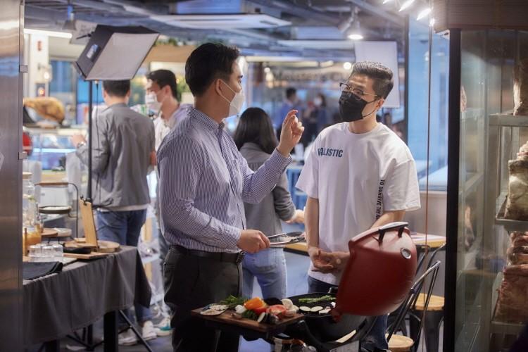 메징 뒷편에서 마스크를 쓴 매장 매니저와 스페셜 게스트 고기 크리에이터 정육왕이 불판을 사이에 두고 고기 관련 이야기를 나누고 있다.