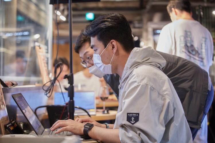 촬영장 한 쪽에 설치된 간이 테이블에 노트북을 올려놓고 상품 판매 수치를 확인하는 MD들의 모습이다.