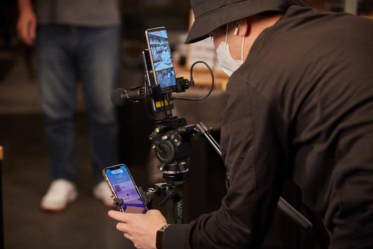 검은색 모자와 옷을 입은 카메라 감독이 거치대에 설치된 스마트폰 3개를 확인하고 있다.