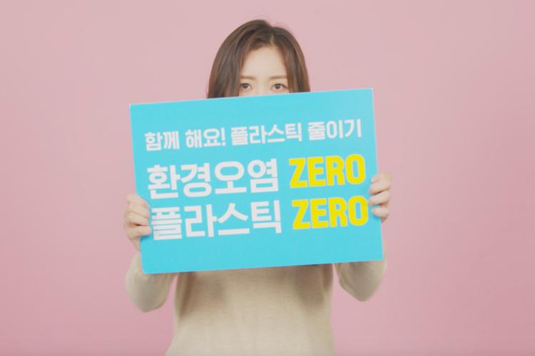 핑크색 배경을 등 뒤로, 아이보리 니트를 입은 한 여성이 파란색 바탕에 '함께 해요! 플라스틱 줄이기 환경오염 ZERO 플라스틱 ZERO' 텍스트가 삽입된 판넬을 들고 있다.