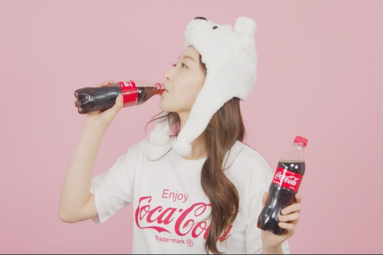 핑크색 배경을 등 뒤로, 코카콜라 티셔츠와 북극곰 모자를 쓴 한 여성이 왼손엔 코카콜라 음료를 그냥 들고 있고, 오른손에 들고 있는 코카콜라 음료는 마시고 있다.