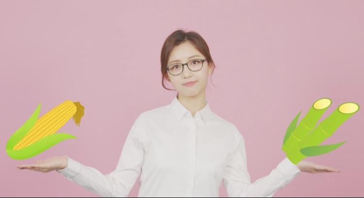 핑크색 배경으로 안경을 쓴 한 여성이 양 손을 펼치고 있고, 그 위에 일러스트 이미지로 옥수수와 대나무가 삽입되어 있다.