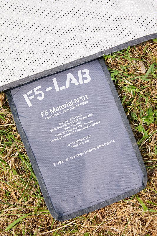 'CGV 스크린 매트'에 붙어 있는 블랙 라벨의 모습으로, 'F5 - LAB' 텍스트와 '본 상품은 CGV 폐스크린을 재사용하여 제작되었습니다'라는 안내 문구가 삽입되어 있다.