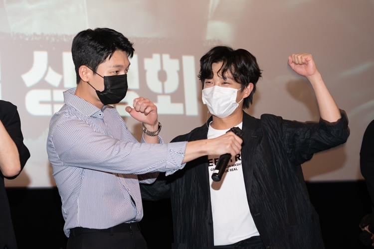 주먹을 쥔 채 손을 들고 있는 김민석과 김민석에게 마이크를 건네는 위하준의 모습