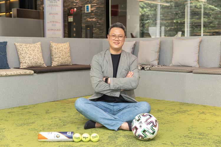 CJ ENM IP유통) 스포츠사업국 구교은 국장이 인조잔디색 바닥에 앉아 2021 프랑스오픈 공인구와 유로 2020 공인구를 앞에놓고 팔짱을 낀 채로 정면을 쳐다보고 있다.