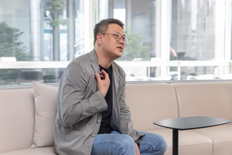 CJ ENM IP유통) 스포츠사업국 구교은 국장이 검은색 테이블을 앞에 두고 소파에 앉아 인터뷰에 응하고 잇다.