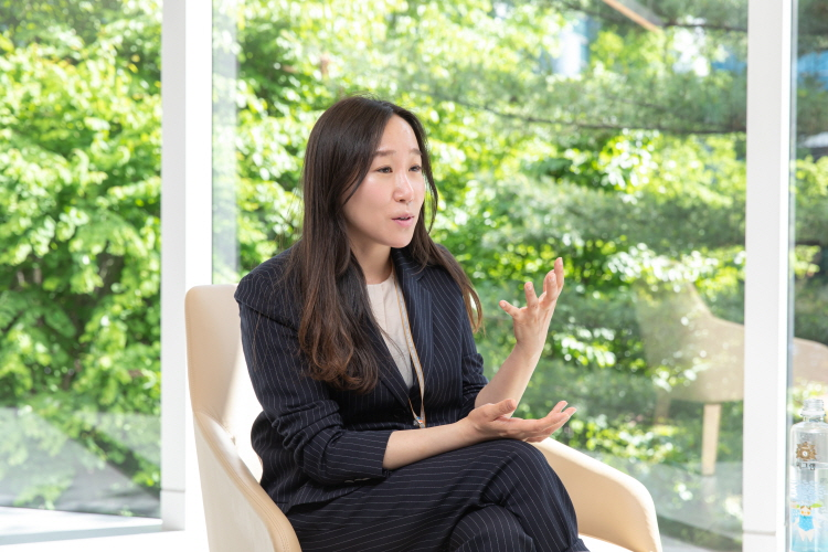 스트라이프 검은색 정장을 입은 CJ ENM IP운영)IP운영3팀 강지훈 팀장이 녹색 나무가 보이는 창가 의자에 앉아 손짓을 하며 이야기를 나누고 있다.