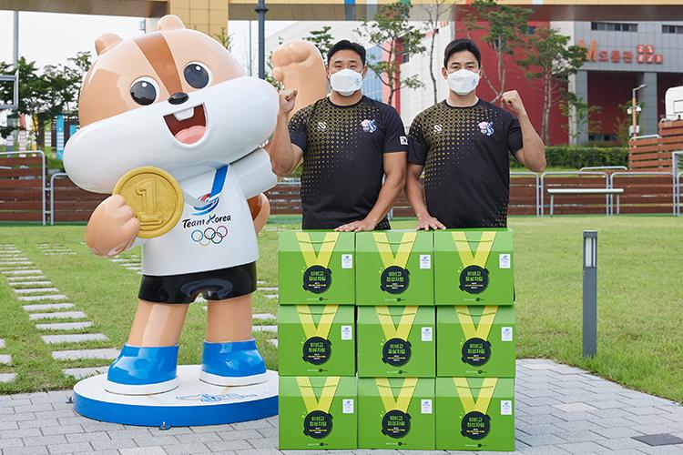 CJ제일제당은 선수들이 대회 기간 중 일본 현지에서 든든한 한 끼를 챙겨 먹을 수 있도록 비비고와 고메 제품을 전달한 모습으로 비비고, 고메 제품이 쌓아올려진 곳에서 두 남자 국가대표가 화이팅 포즈를 취하고 있다.
