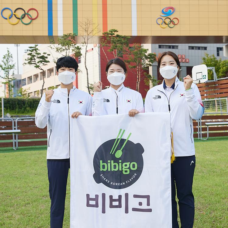 CJ제일제당은 선수들이 대회 기간 중 일본 현지에서 든든한 한 끼를 챙겨 먹을 수 있도록 비비고와 고메 제품을 전달한 이미지로 세 명의 여성 국가대표가 화이팅 포즈를 취하며 비비고 로고 현수막을 들고 있다.