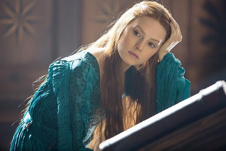 영화 '오필리아'에서 오필리아 역을 맡은 데이지 리들리의 모습으로 긴 머리에 청록색 옷을 입고 손으로 머리를 받치며 고민에 잠겨있다.