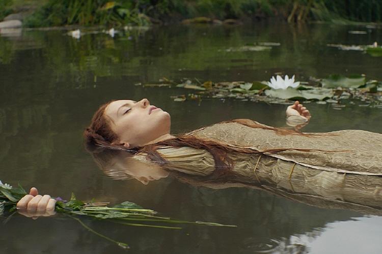 오필리아가 눈을 감고 연못 물에 뜬 모습으로 양 팔을 벌린 채오른손에는 들꽃을 들고 있다.