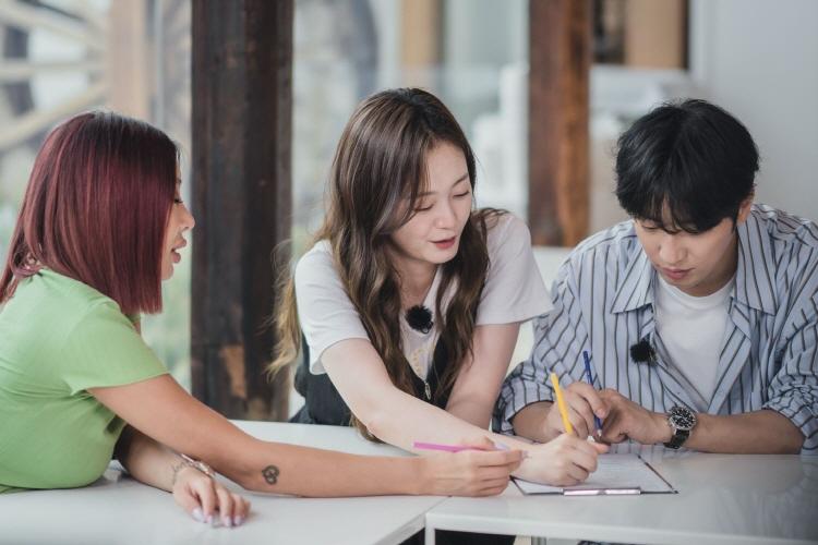 신박한 아이디어 식당 중 한 곳을 방문한 (왼쪽부터) 제시, 전소민, 이상엽이 의자에 앉아 테이블 위에 놓인 제출지에 각자 펜으로 뭔가를 쓰려고 하고 있다.