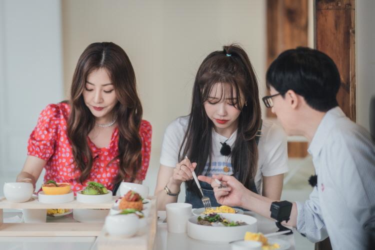신박한 아이디어 식당 중 한 곳을 방문한 (왼쪽부터) 오나라, 이미주, 유재석은 테이블 위 마련된 음식을 먹으려고 하고 있다. 오나라, 이미주는 포크로 음식을 먹으려고 하고 있고, 유재석은 누군가 이야기를 나누고 있다.