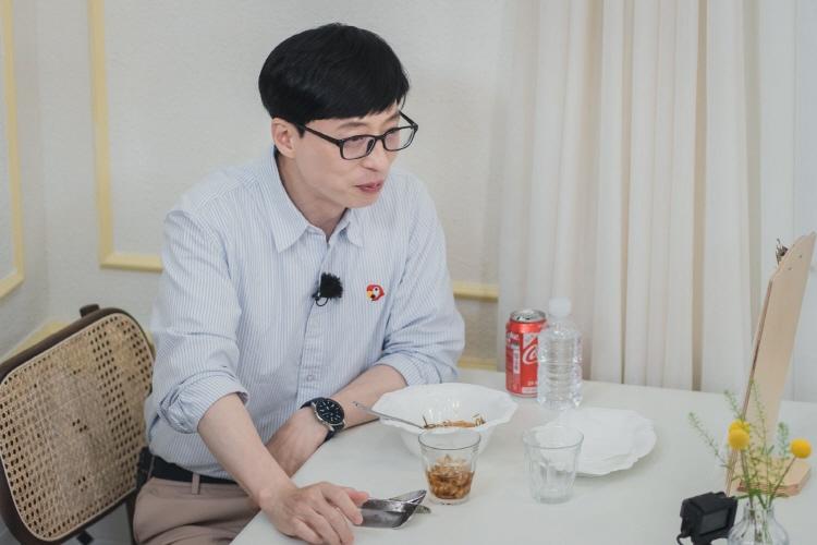 신박한 아이디어 식당 중 한 곳을 방문한 유재석은 테이블에 앉아 음식을 먹고 뭔가 묘한 미소를 짓고 있다.