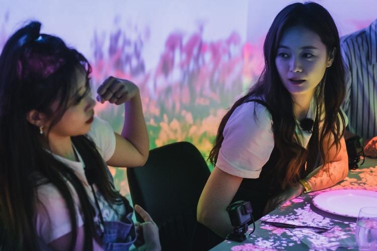 3D 맵핑 식당을 방문한 이미주, 전소민이 테이블에 앉아 이야기를 나누고 있다. 테이블 및 벽엔 영상으로 구현된 꽃들이 만발하고 있다.
