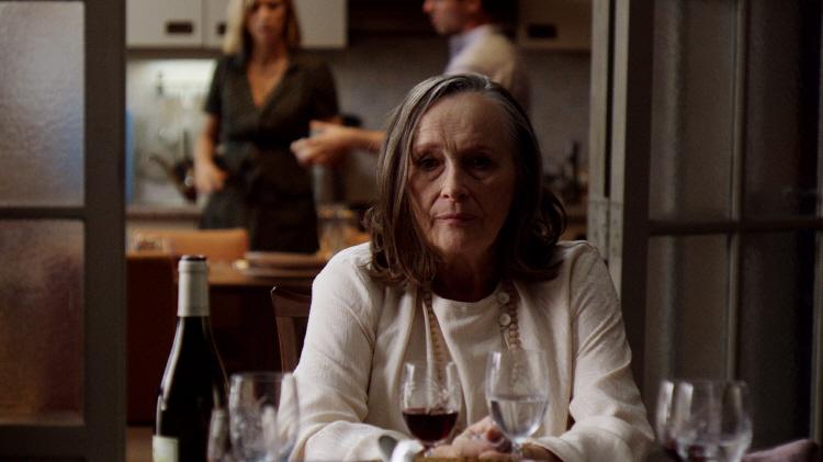 식탁에 앉아 어디론가 물끄러미 쳐다보고 있는 마노와 그 뒤에 서 있는 그녀의 자식들의 모습이 보인다.