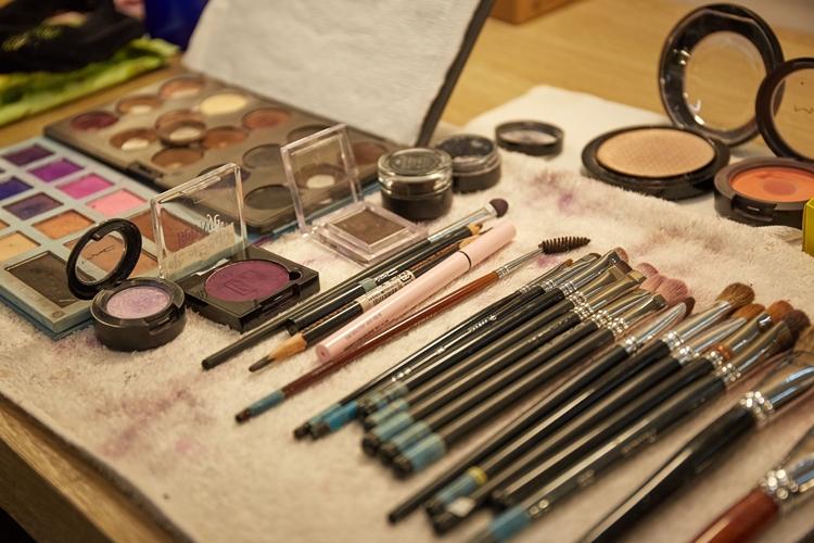 분장 도구들이 수건 위에 가지런히 놓인 모습. 색조 화장에 쓰이는 쉐도우들과 붓 등의 도구가 놓여있다.