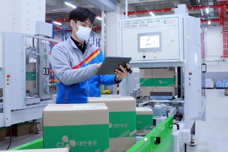 CJ대한통운 유니폼을 입은 작업자가 군포 e-풀필먼트 센터에서 물류 작업을 수행하고 있다. 박스 중앙 녹색 부분은 CJ대한통운 로고가 삽입되어 있고, 레일 위에 총 4개의 크기가 다른 박스가 물류 기계 앞에서 대기하고 있다. 작업자 손에는 이 태블릿 PC를 보며 하나씩 체크를 하고 있다.