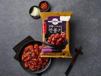 회색 식탁에 '고메 바삭촉촉한 깐풍기' 제품과 검은색 그릇에 담긴 깐풍기와 단무지, 김치, 그리고 젓가락이 놓여 있다.