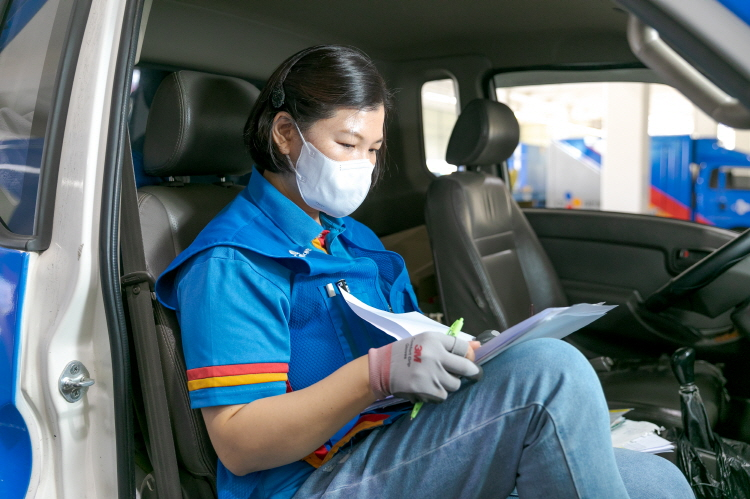 CJ대한통운 부산중구부평대리점 나성미 택배기사가 택배 차량 보조석에 앉아 왼손에는 관련 서류, 오른손에는 볼펜을 들고 서류 업무를 보고 있다.