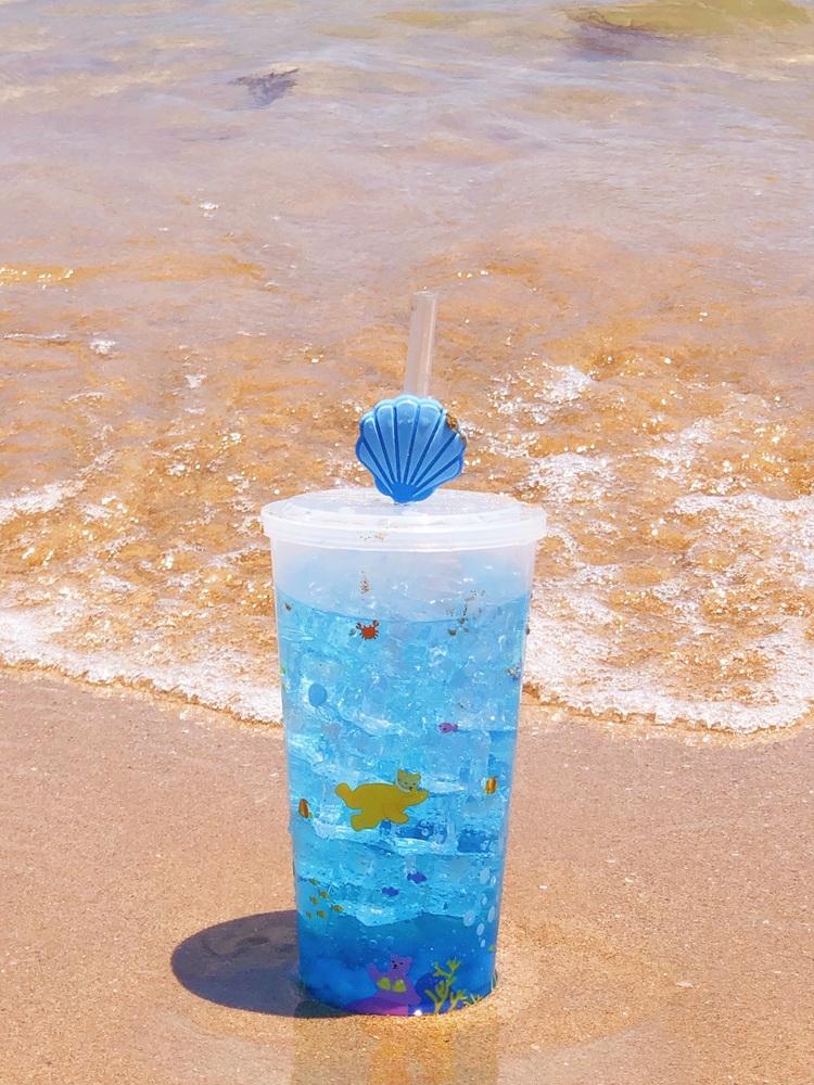 바닷가 해변에 무더운 여름 시즌을 겨냥해 최근 출시한 음료 '바다에 갓-소다'는 젤리베어와 콜라보한 리유저블컵이 놓여있다. 재사용이 가능한 리유저블컵은 바다 속을 헤엄치는 젤리베어와 함께 상큼하게 음료를 즐길 수 있어 집에서도 시원한 바다 풍경을 느낄 수 있다. 시원한 바다를 연상시키는 푸른 계열의 은은한 오렌지맛 에이드 '바다에 갓-소다'는 탱글탱글한 나타드 코코가 들어있어 씹는 재미까지 맛볼 수 있다.