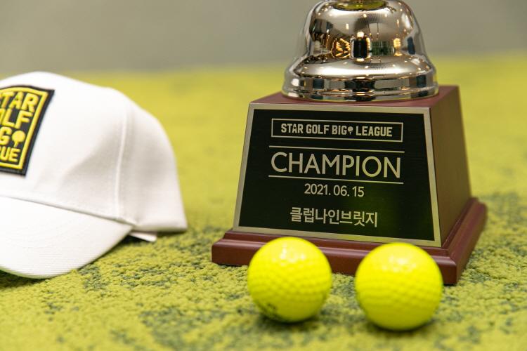 그린 카펫 위에 tvN D '스타골프빅리그' 공식 트로피와 골프공, 모자가 놓여있다. 트로피 내에는 star golf big league CHAMPION 2021.06.15 클럽나인브릿지 텍스트가 삽입되어 있다.