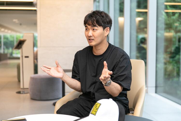 tvN D '스타골프빅리그' 김영창 PD가 검은색 옷을 입고 의자에 앉아 손을 들면서 인터뷰에 응하고 있다.