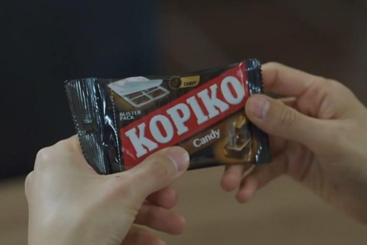 양 손으로 사탕 봉지를 들고 있는 모습. 사탕 봉지에는 짙은 갈색 봉지 가운데 붉은 평행사변형이 대각선으로 있고, 그 위에 KOPIKO라는 상품명이 흰색으로 적혀있다.