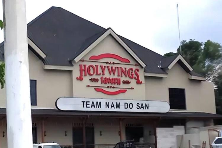 삼각형으로 솟은 세개의 짙은 회색 지붕과 베이지색으로 이뤄진 건물 가운에 붉은 글씨로 HOLYWINGS tavern이라 적혀있고 그 아래 TEAM NAM DO SAN이라는 간판이 걸려있다.