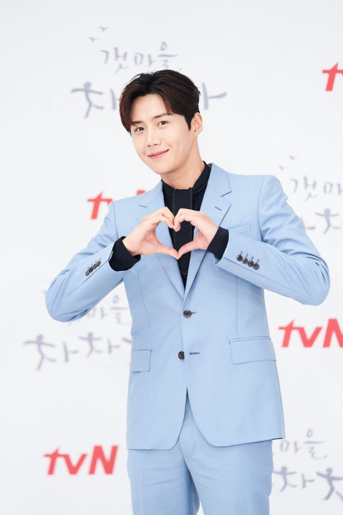 하늘색 수트를 입은 배우 김선호가 카메라를 향해 두 손으로 하트를 만든다. 입가엔 은은한 미소를 띄고 있다.