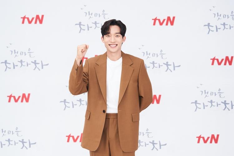 갈색 캐주얼 수트를 입은 배우 이상이가 활짝 웃으며 카메라를 응시하고 있다. 한 쪽 손은 화이팅을 의미하는 주먹을 쥐고 있다.