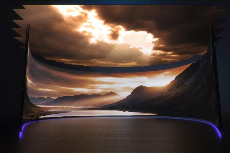 CJ ENM 버추얼 스튜디오의 컨셉 이미지. 타원형의 무대를 스크린이 둥글게 감싸고 있고, 스크린에 산 사이로 햇빛이 비치는 풍경이 펼쳐진다. 무대 위 천장에도 구름 사이로 빛이 비치고 있다.