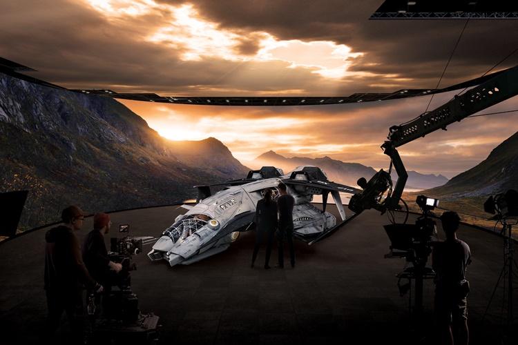 원형의 스튜디오 바닥을 둘러싼 천장 스크린과 벽면 스크린에 산과 구름 사이로 햇빛이 비치는 풍경이 펼쳐지고 스튜디오 바닥 한 가운데 우주선과 같은 기계가 놓여있다. 그 주변으로 스탭들이 있고, 촬영을 진행하는 모습.