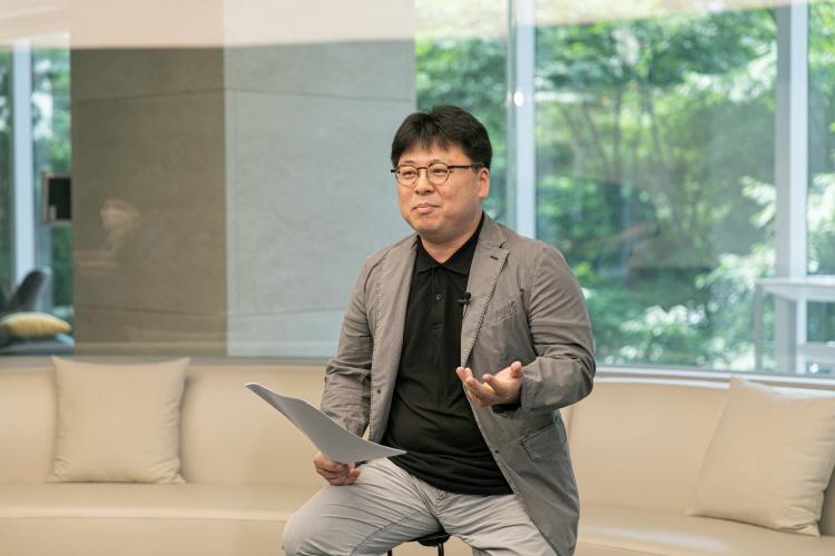 CJ ENM IP유통본부 유통전략담당 김종백 님이 아이보리 색 라운드 소파에 앚아 종이를 들고 뭔가를 말하고 있다.