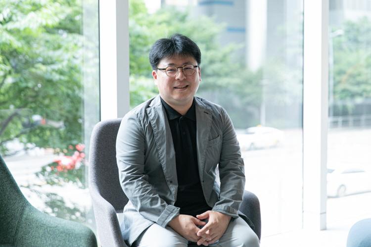 CJ ENM IP유통본부 유통전략담당 김종백 님이 회색 의자에 앉아 손을 모으고 카메라를 쳐다보고 있다.